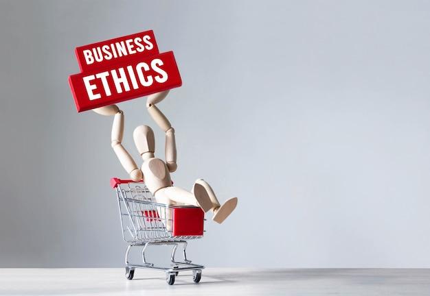Drewniany człowiek trzyma czerwony drewniany klocek ze słowem etyka biznesu, koncepcja.