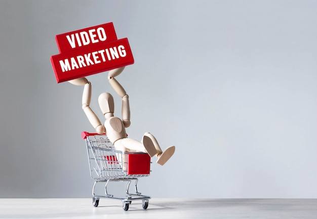 Drewniany człowiek trzyma czerwony drewniany klocek ze słowem video marketing, koncepcja.