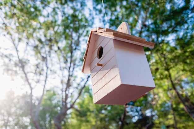 Drewniany dom dla małych ptaków wisi na drzewie w ogrodzie.