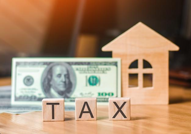 Drewniany dom i banknot stu dolarów, podatki na napisy. pojęcie podatku od nieruchomości