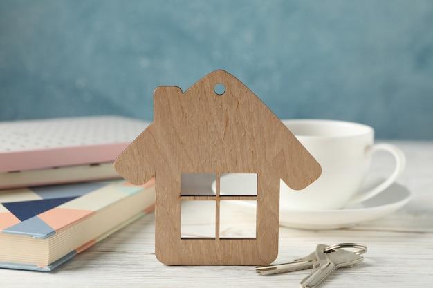 Drewniany dom i klucze na drewnianej powierzchni. miejsce pracy