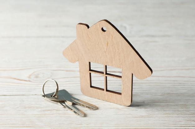 Drewniany dom i klucze na drewnianej powierzchni, zamykamy up