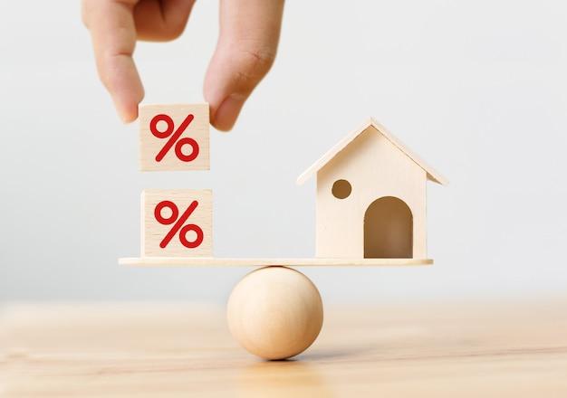 Drewniany dom i ręka umieszczenie kształtu kostki z ikoną procent
