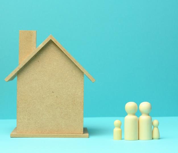Drewniany dom i samochód z miniaturowymi postaciami rodzinnymi, koncepcją kredytu hipotecznego i pożyczki, z bliska