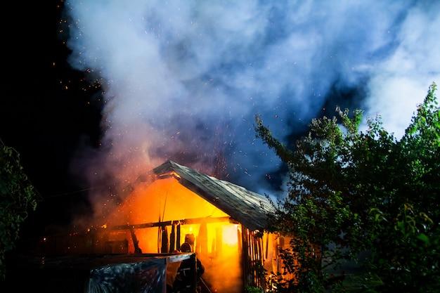 Drewniany dom lub stodoła płonąca w nocy.