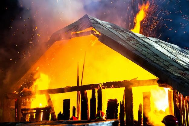 Drewniany dom lub stodoła płonąca w nocy