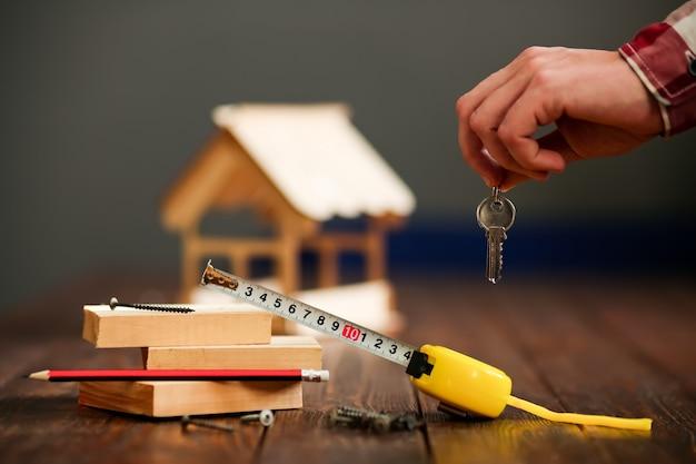 Drewniany dom na drewnianej powierzchni z desek i pęku kluczy z chipem. koncepcja - budowa domu pod klucz. wysokiej jakości zdjęcie