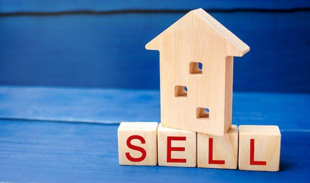 Drewniany dom na niebieskim tle z napisem sprzedać.