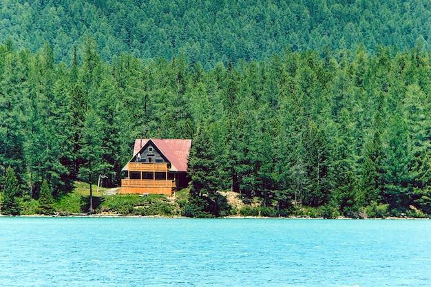 Drewniany dom nad błękitnym jeziorem w gęstym lesie wśród drzew. baza turystyczna w syberyjskiej tajdze. dom z drewnianą ramą. ałtaj. rosja.