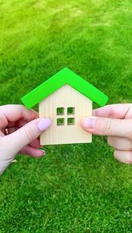 Drewniany dom w rękach młodej rodziny.