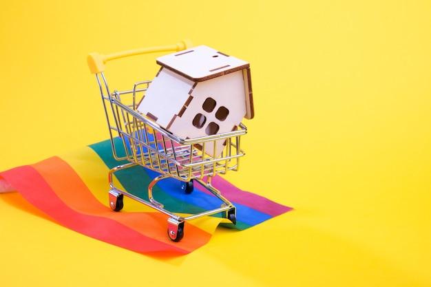 Drewniany dom w wózku sklepowym stoi na fladze społeczności lgbt