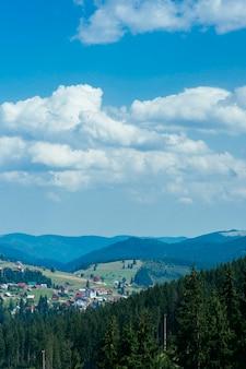 Drewniany dom w zielonych górach z niebieskim niebem i chmurami