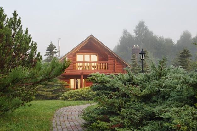 Drewniany dom wśród drzew o wschodzie słońca w lecie