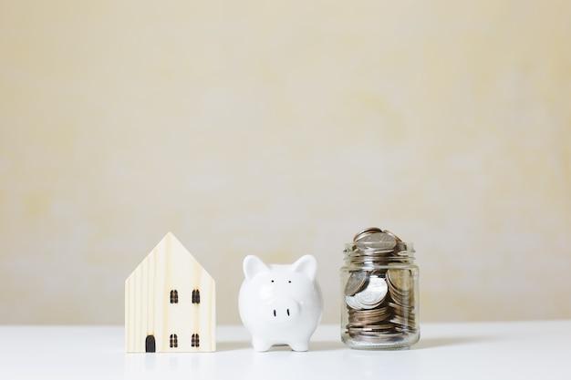 Drewniany dom z białą skarbonką i monetami pieniędzy w szklanym słoiku na stole, inwestycje w nieruchomości, oszczędzanie na przyszłość, pieniądze inwestycja na zakup domu. koncepcja biznesowa inwestycji.