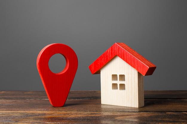 Drewniany dom z figurkami i czerwony wskaźnik lokalizacji.