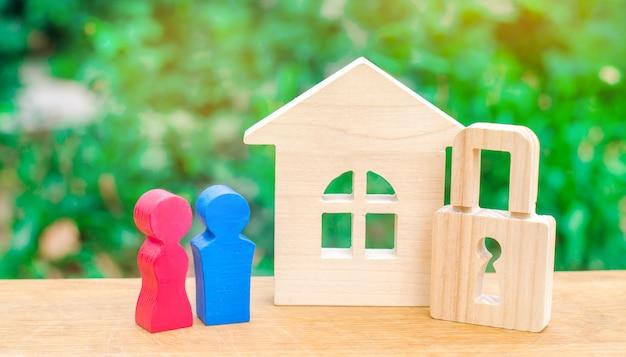 Drewniany dom z kłódką i młodą parą kochanków.