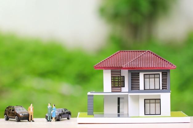 Drewniany dom z miniaturowymi ludźmi stojącymi i samochodem