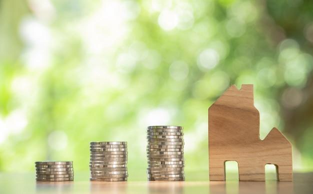 Drewniany dom z monetami na drewnianym stole