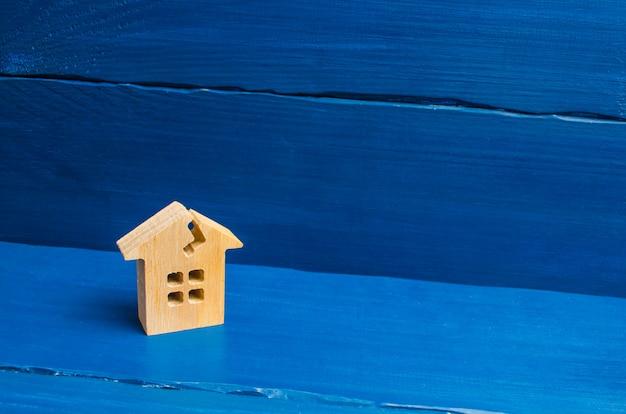Drewniany dom z pęknięciem. pojęcie uszkodzonego domu, zrujnowanego mieszkania.