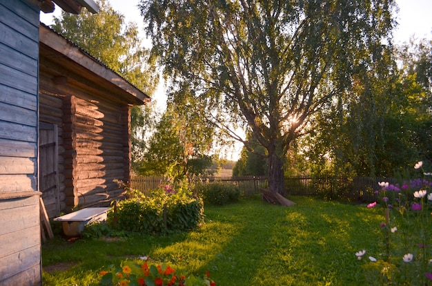 Drewniany dom z rzeźbionymi oknami w wołogdzie w rosji. rosyjski styl w architekturze. nieociosany rosyjski dom z ogródem