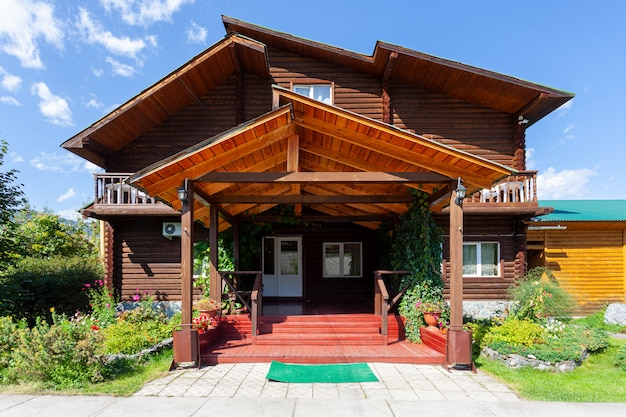 Drewniany dom z werandą i zieloną trawą, błękitne niebo i promienie słoneczne.