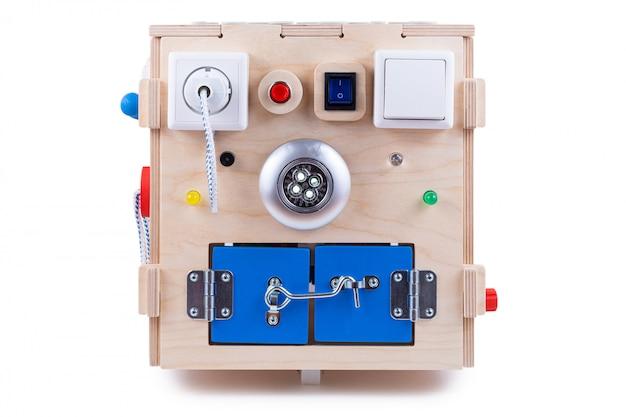 Drewniany dom - zabawka edukacyjna dla dzieci, niemowląt na białym tle, składająca się z wielokolorowych drewnianych puzzli, labiryntu, sprzętu, sortownika, przełączników, gniazdka, lampy, drewnianego zegara
