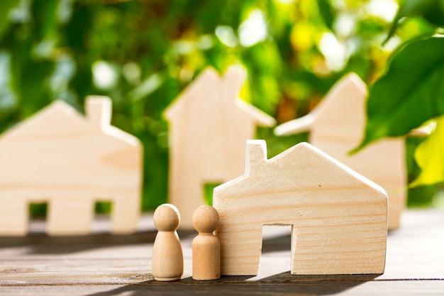 Drewniany dom zabawki i drewniana rodzina na liściach