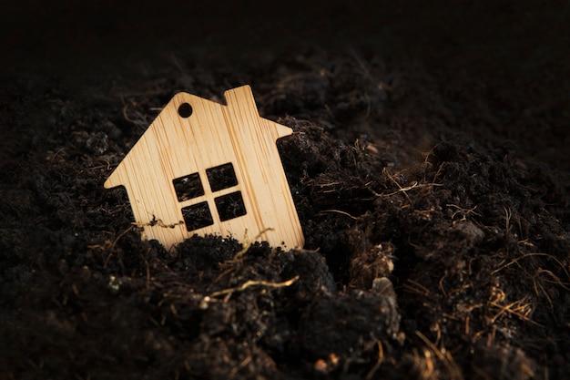 Drewniany dom zapada się w ziemię. hipoteka pod ziemią, dom na sprzedaż, koncepcja kryzysu nieruchomości, kopia przestrzeń. winien zadłużony. kryzys hipoteczny. przestępca traci nieruchomość. strata domu obciążonego hipoteką