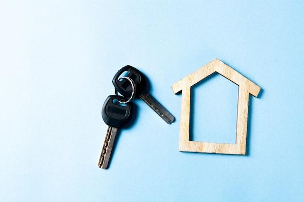 Drewniany domek i klucze na niebieskiej powierzchni