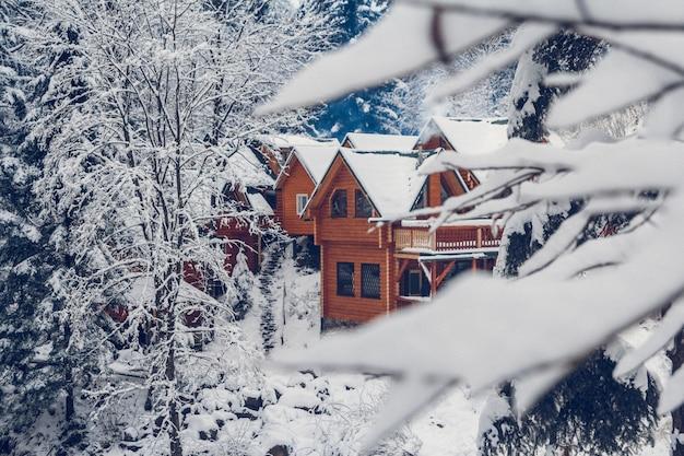 Drewniany domek letniskowy w górskiej miejscowości wypoczynkowej pokrytej świeżym śniegiem