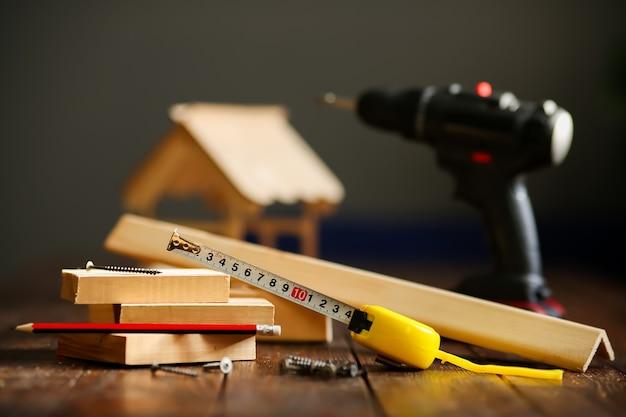 Drewniany domek na drewnianej powierzchni wykonany z desek i narzędzi, taśma miernicza, śrubokręt, ołówek. koncepcja - budowa domu pod klucz. wysokiej jakości zdjęcie