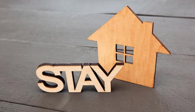"""Drewniany domek na drewnianym biurku i napis """"zostań"""" obok niego. zostań w domu, aby przestać rozprzestrzeniać wirusa, zmniejsz ryzyko infekcji. chroń świat przed koronawirusem"""