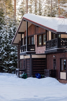 Drewniany domek w pobliżu lasu sosnowego, pokryty śniegiem
