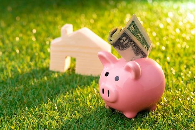 Drewniany domek z zabawkami i skarbonka, oszczędzając pieniądze na dom