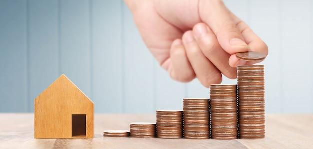 Drewniany domek z zabawkami nieruchomość hipoteczna dom kupowanie dla rodziny, monety w ręku