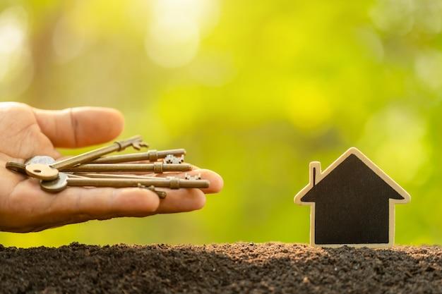 Drewniany domowy dorośnięcie w ziemi i rocznika kluczu na zielonej naturze zamazujemy tło. klucz do sukcesu w biznesie domowym dorasta koncepcja