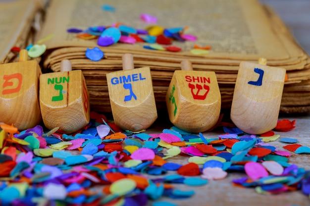 Drewniany dreidels spinning top dla żydowskiego święta chanuka nad tłem brokatu
