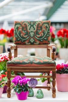 Drewniany fotel z materiałową tapicerką i kwiatami w tle