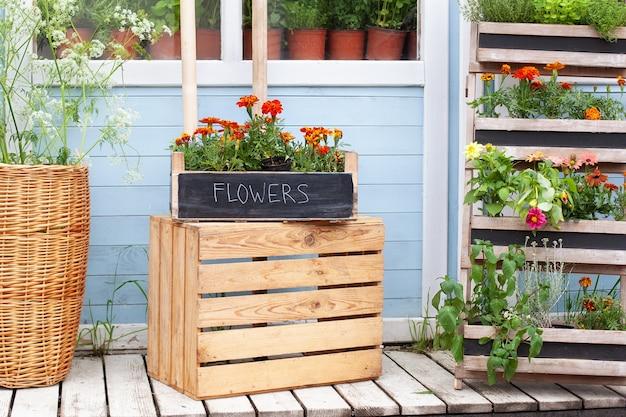 Drewniany ganek domu z zielonymi roślinami i kwiatami fasada domu z narzędziami ogrodowymi i kwiatami doniczkowymi