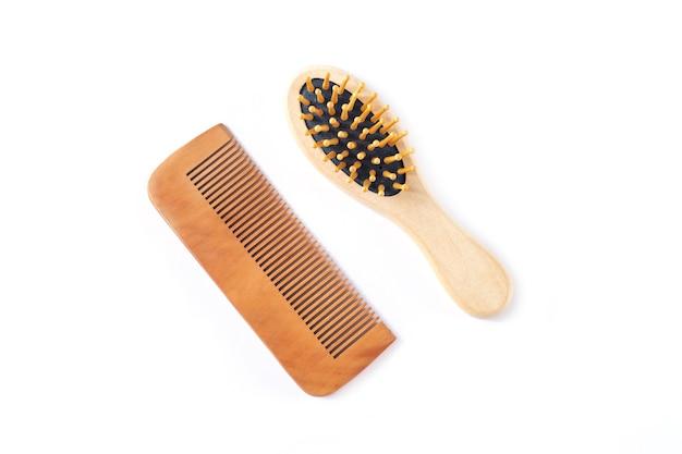 Drewniany grzebień do pielęgnacji włosów i szczotka do masażu na białym tle
