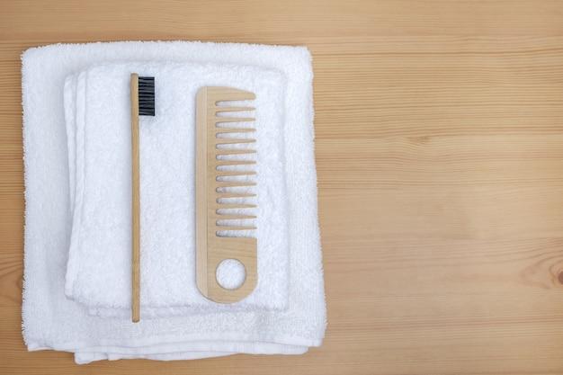 Drewniany grzebień i szczoteczka do zębów na białym ręczniku