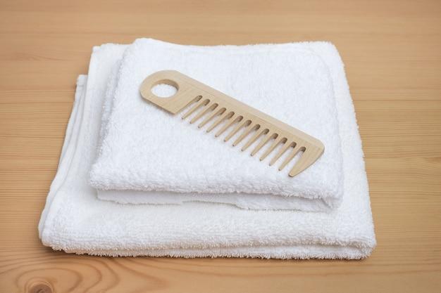 Drewniany grzebień na białym ręczniku