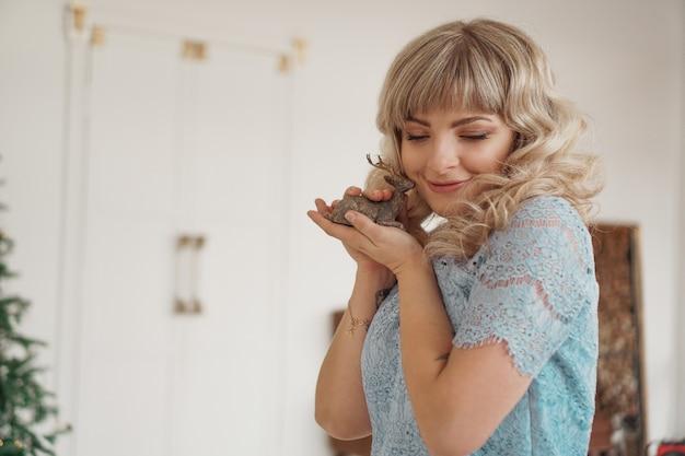 Drewniany jeleń w rękach młodej blondynki. szczęśliwa kobieta szykuje się na nowy rok