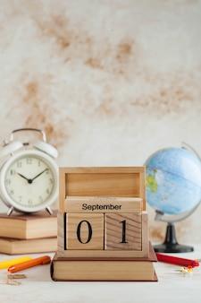 Drewniany kalendarz 1 września na książce, świecie, budziku. dzień wiedzy, początek roku szkolnego. skopiuj miejsce