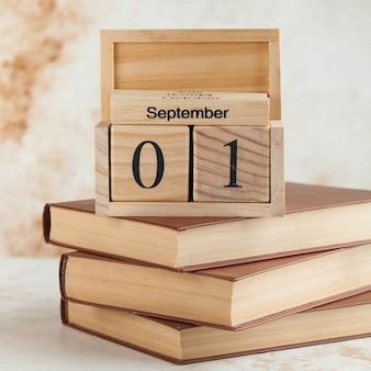 Drewniany kalendarz 1 września na stosie książek. koncepcja dnia wiedzy, początek roku szkolnego.