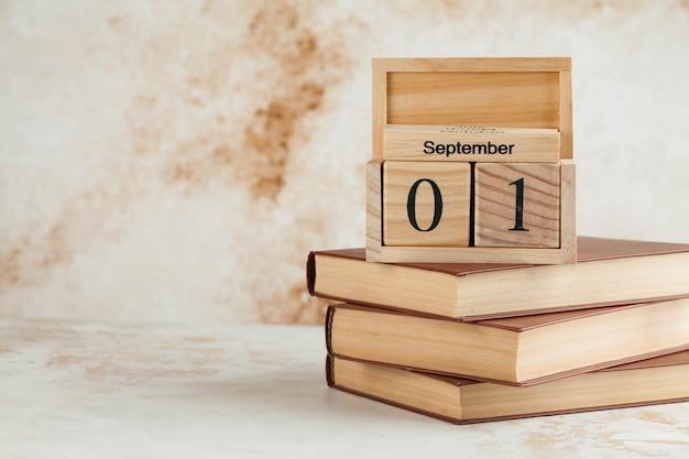 Drewniany kalendarz 1 września na stosie książek. koncepcja dnia wiedzy. skopiuj miejsce.