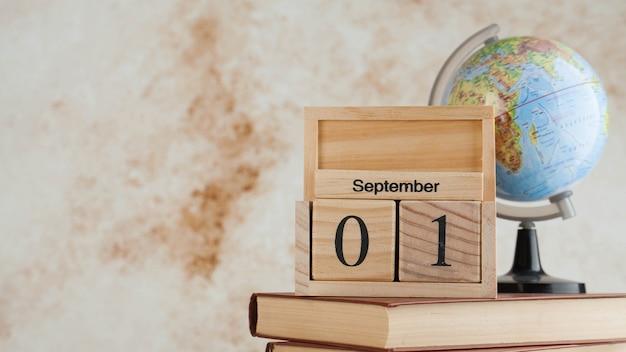 Drewniany kalendarz 1 września na stosie książek, na świecie. koncepcja dnia wiedzy, początek roku szkolnego. skopiuj miejsce.