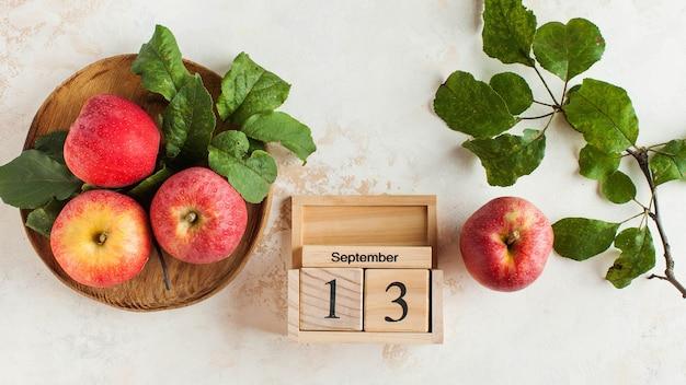 Drewniany kalendarz 13 września i jabłka. wakacje jesienne, święto jesiennych ciast i charlotte.