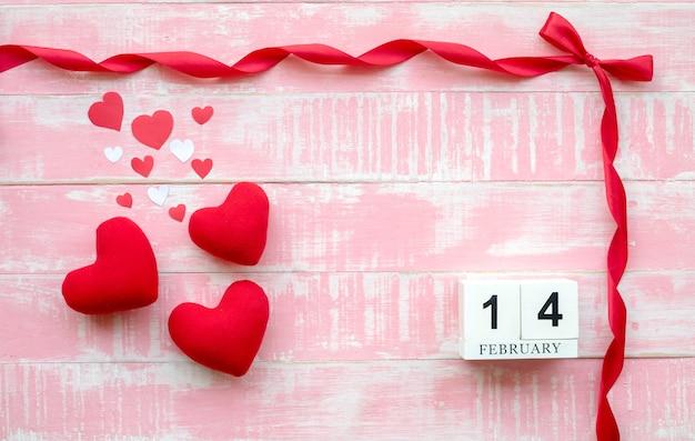 Drewniany kalendarz 14 lutego składa się z czerwonej wstążki i serca