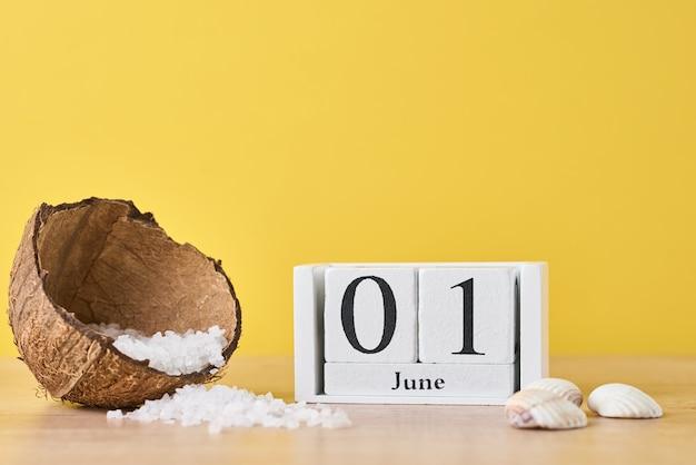 Drewniany kalendarz blokowy z datą 1 czerwca i kokosem z solą morską na żółtym tle. koncepcja wakacji letnich